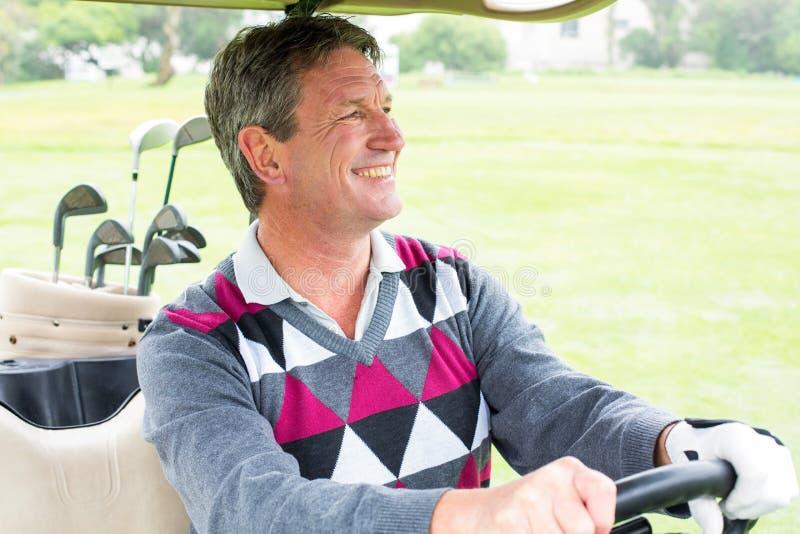 Szczęśliwy golfista jedzie jego golfowy powozik zdjęcie royalty free
