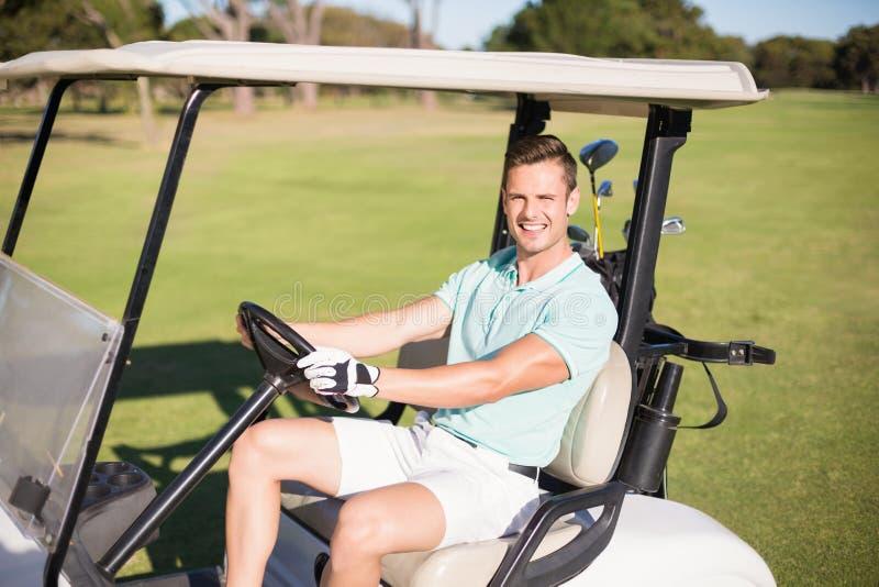 Szczęśliwy golfisty mężczyzna jeżdżenia golfa powozik zdjęcie royalty free