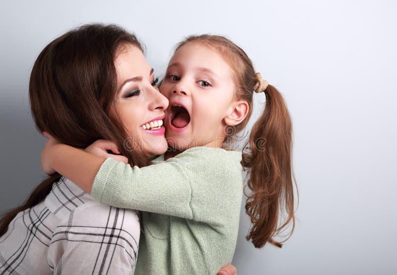 Szczęśliwy grimacing dzieciak chce gryźć jej roześmianej matki w nie zdjęcia stock