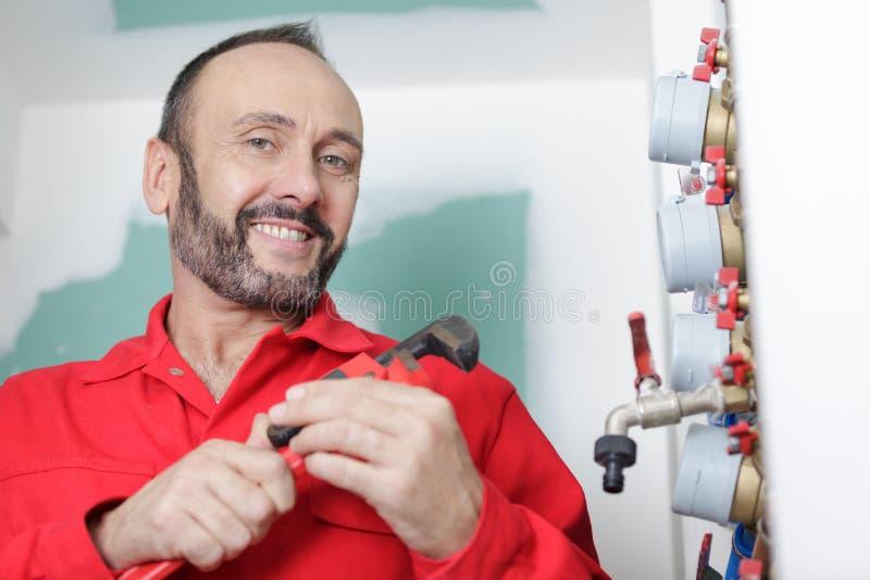 Szczęśliwy hydraulik instaluje ciśnieniowego metr dla domu zdjęcia royalty free