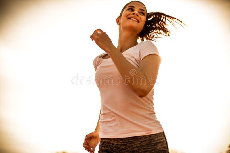 Szczęśliwy i podnoszący na duchu bieg przy słonecznym dniem młode kobiety zdjęcia royalty free