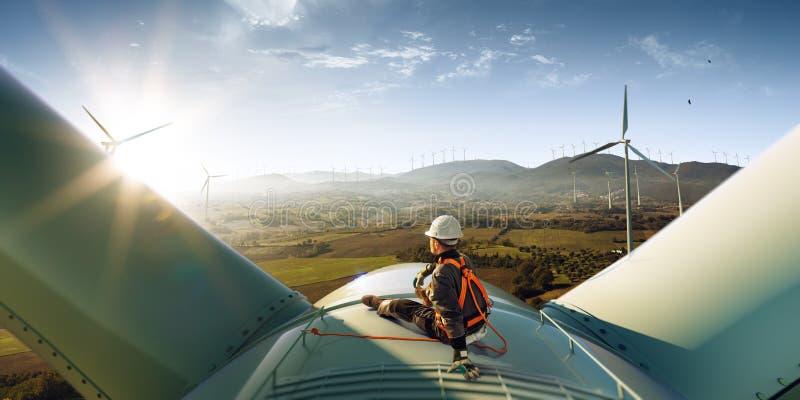 Szczęśliwy inżyniera odczucia sukces po dobrej pracy On stoi wierzchołek wiatraczek i przyglądający piękny zmierzch zdjęcie royalty free