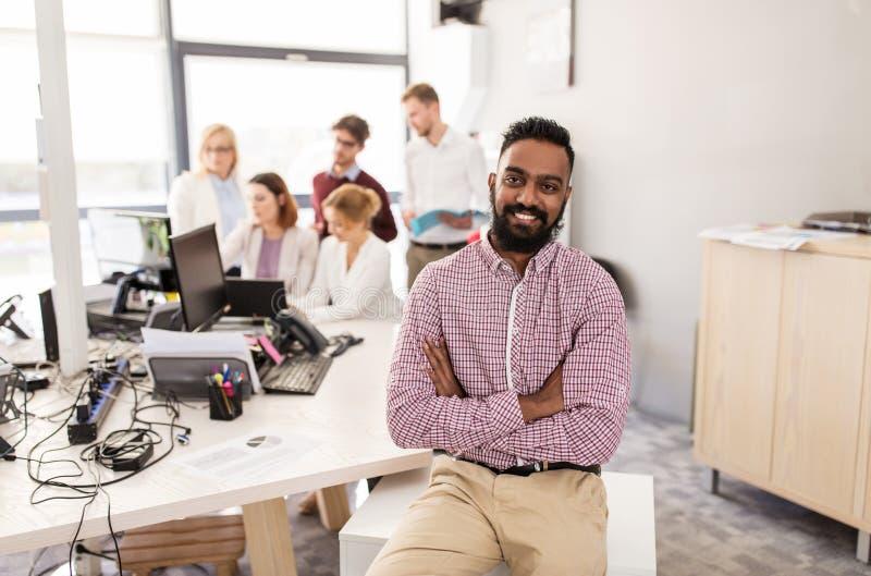 Szczęśliwy indyjski mężczyzna nad kreatywnie drużyną w biurze fotografia royalty free