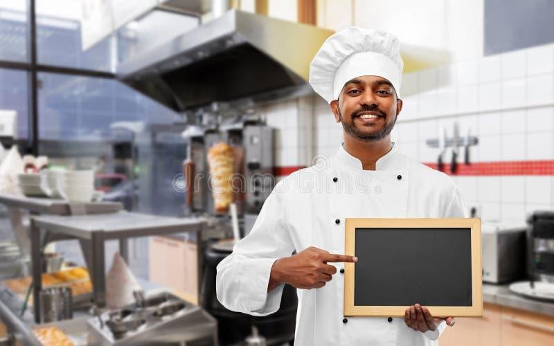 Szczęśliwy indyjski szef kuchni z chalkboard przy kebabu sklepem obraz stock