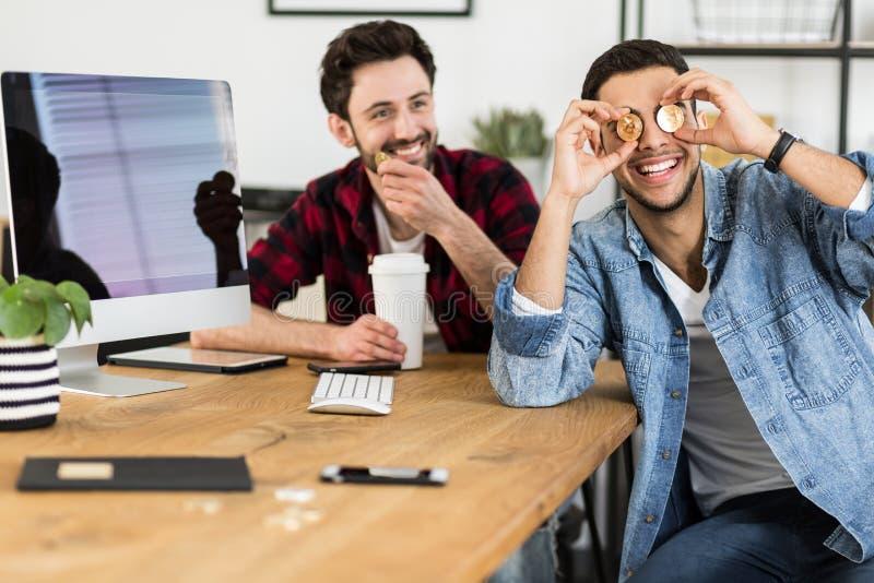 Szczęśliwy inwestor z złocistymi BitCoin monetami podczas gdy kupujący wirtualnego mone fotografia stock