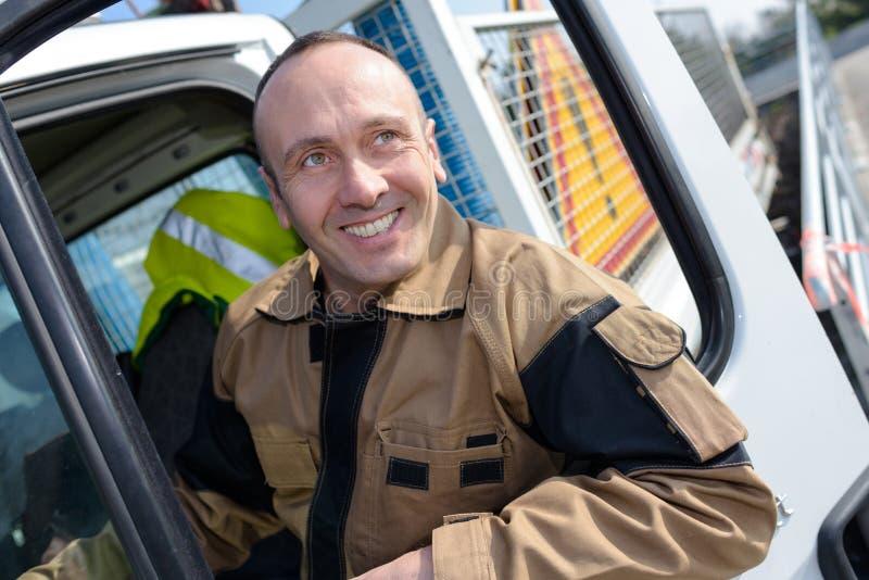 Szczęśliwy kierowca ciężarówki ono uśmiecha się przy kamerą fotografia stock