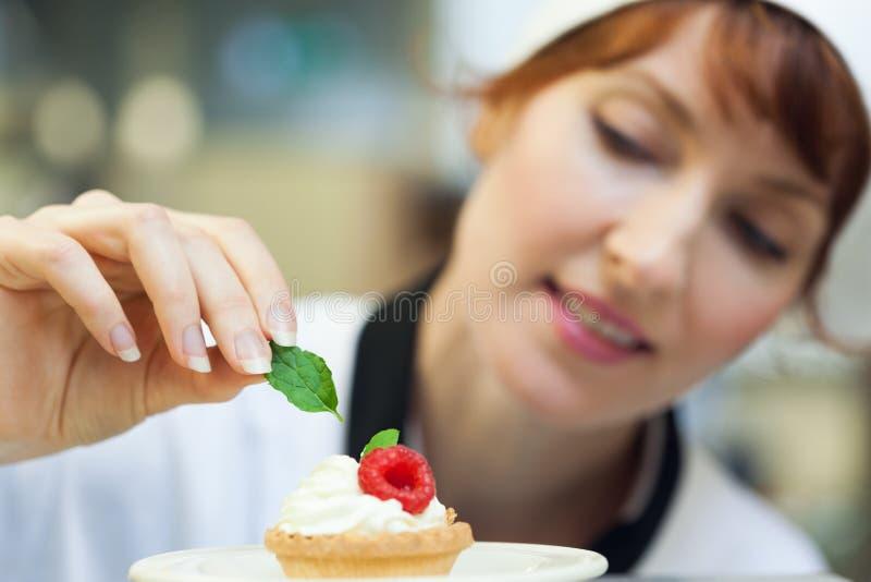Szczęśliwy kierowniczego szefa kuchni kładzenia mennicy liść na małym torcie fotografia stock