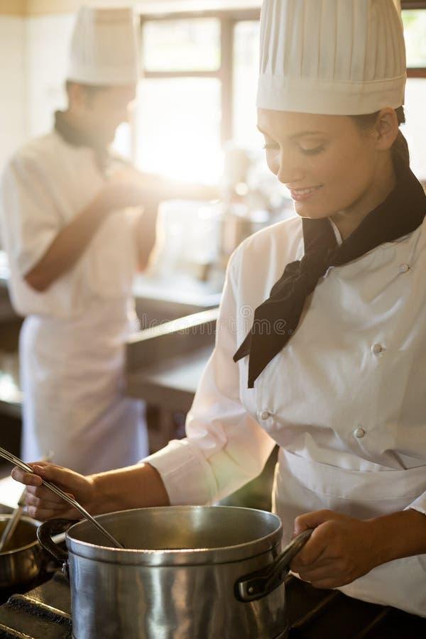 Szczęśliwy kierowniczego szefa kuchni kucharstwo przy kuchenką zdjęcia stock