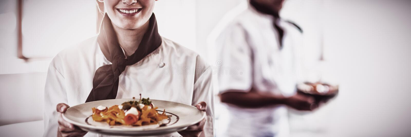 Szczęśliwy kierowniczy szef kuchni przedstawia jej jedzenie fotografia royalty free