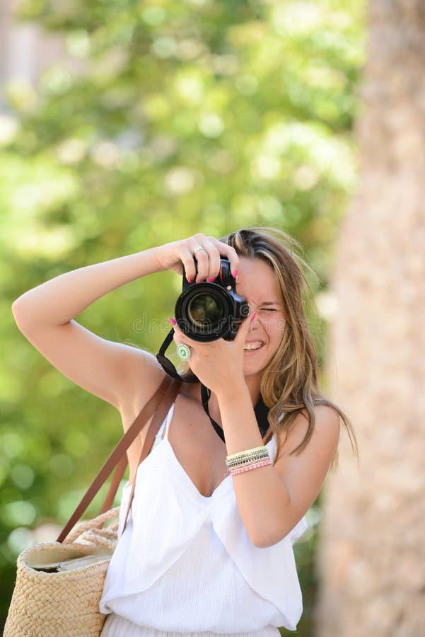 Szczęśliwy kobieta fotograf trzyma dslr kamerę fotografia royalty free