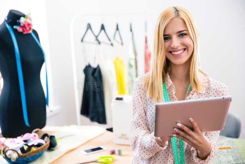 Szczęśliwy kobieta krawczyny mienia pastylki komputer fotografia royalty free