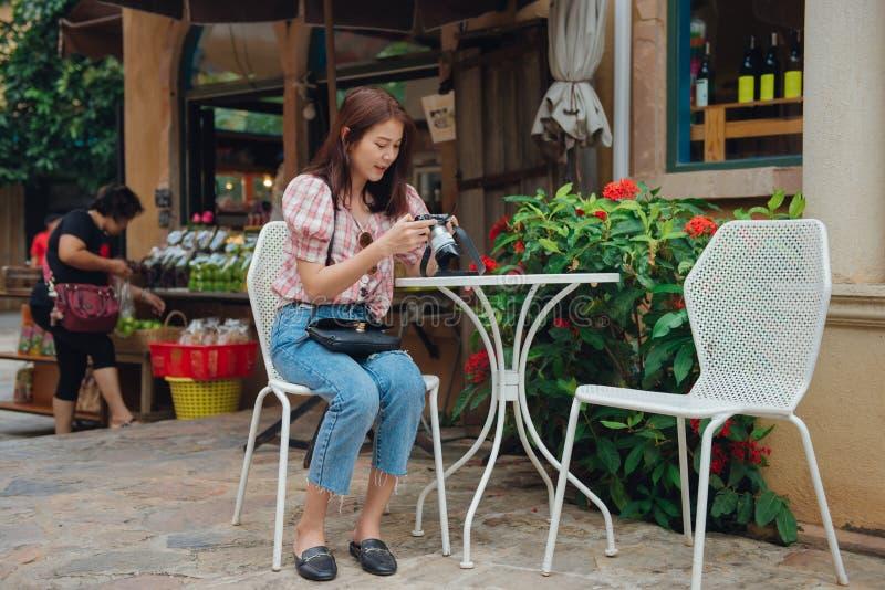Szczęśliwy kobieta podróżnik sprawdza kamery obsiadanie w outdoors kawiarni w retro rocznika mieście zdjęcia stock