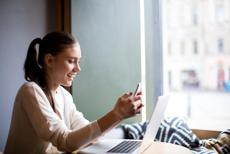 Szczęśliwy kobieta uczeń ma wideo wezwanie przez telefonu komórkowego, siedzi z notatnikiem w sklepie z kawą fotografia royalty free