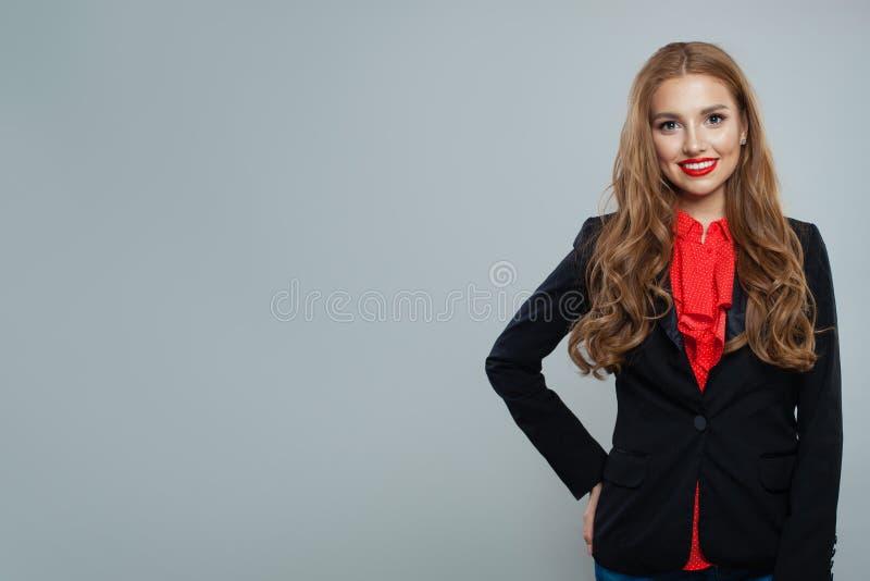Szczęśliwy kobieta uczeń na szarym tle Biznesowa kobieta w czarnym kostiumu portrecie zdjęcie stock