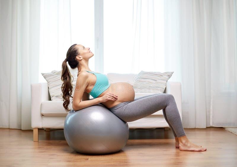 Szczęśliwy kobieta w ciąży ćwiczy na fitball w domu obraz stock