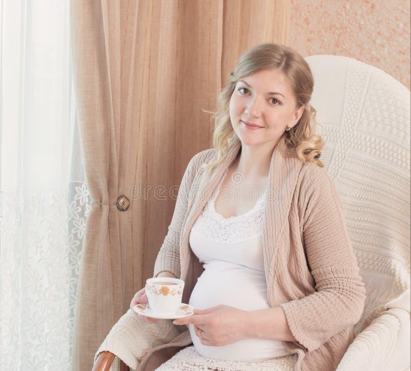 Szczęśliwy kobieta w ciąży pije herbaty z filiżanką obrazy royalty free