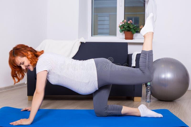 Szczęśliwy kobieta w ciąży robi rozciąganiu ćwiczy w żywym pokoju fotografia royalty free