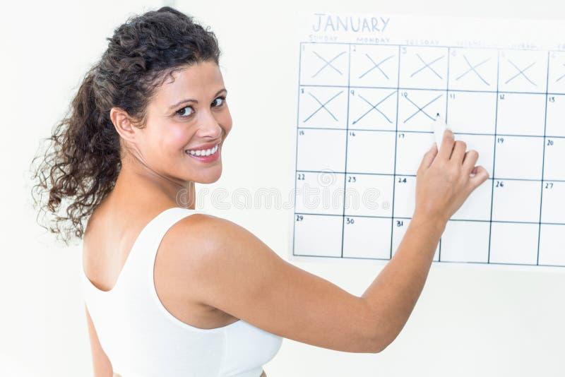 Szczęśliwy kobieta w ciąży zaznacza z dat na kalendarzu zdjęcie royalty free