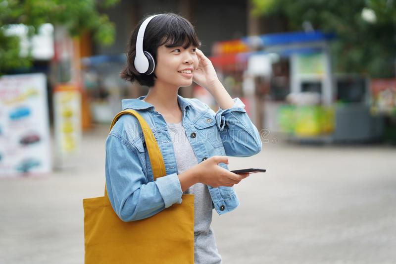 szczęśliwy kobieta zakupy z słuchaniem muzyka na smartphone i mienia dużego ciężaru torbie obraz royalty free