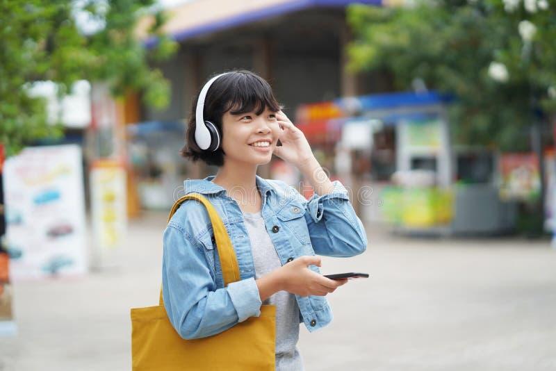 szczęśliwy kobieta zakupy z słuchaniem muzyka na smartphone i mienia dużego ciężaru torbie zdjęcia stock