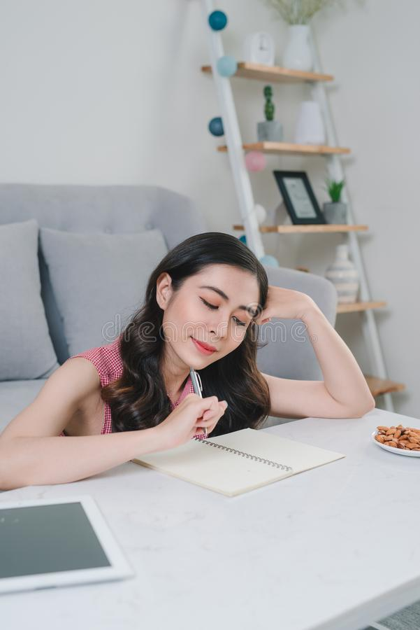 Szczęśliwy kobiety główkowanie co pisać w notatnika obsiadaniu na floo obrazy royalty free