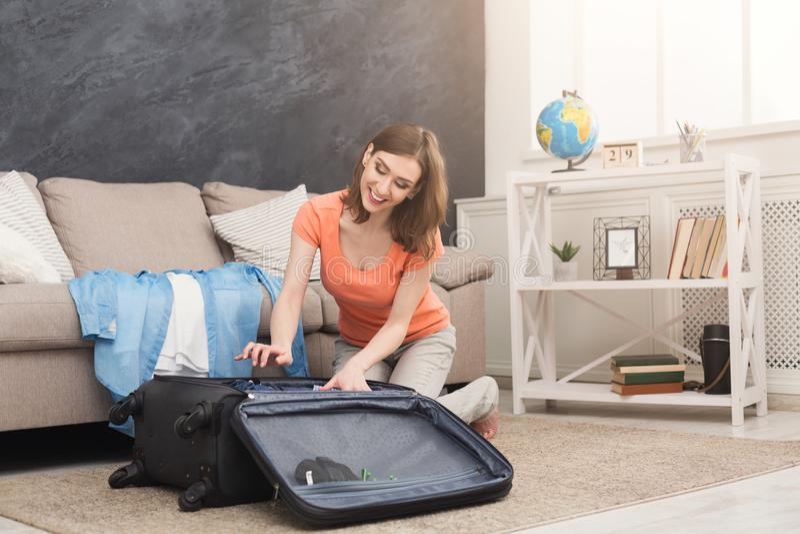 Szczęśliwy kobiety kocowanie odziewa w podróży torbę zdjęcie royalty free