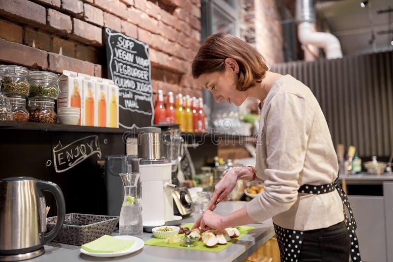 Szczęśliwy kobiety lub barmanki kucharstwo przy weganin kawiarnią zdjęcie royalty free