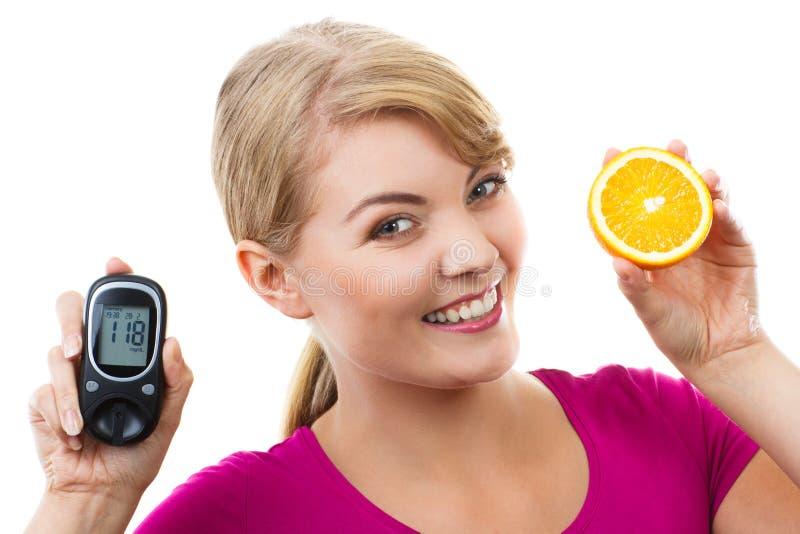 Szczęśliwy kobiety mienia glucometer, świeża pomarańcze i, pojęcie cukrzyce zdjęcia stock
