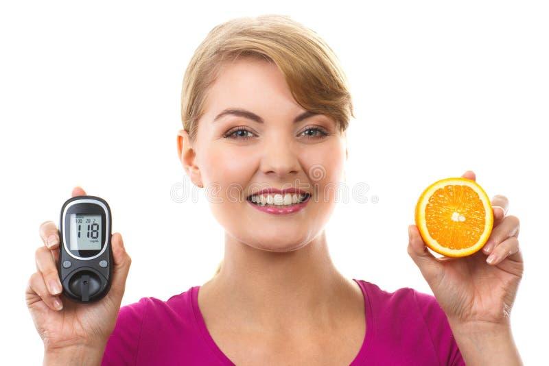 Szczęśliwy kobiety mienia glucometer, świeża pomarańcze i, pojęcie cukrzyce obraz stock
