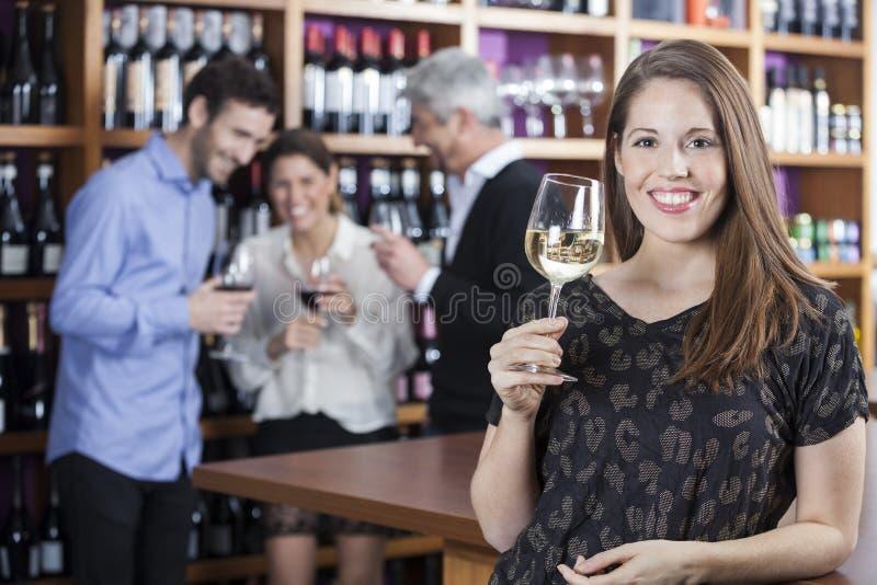 Szczęśliwy kobiety mienia Wineglass Z przyjaciółmi W tle zdjęcie royalty free