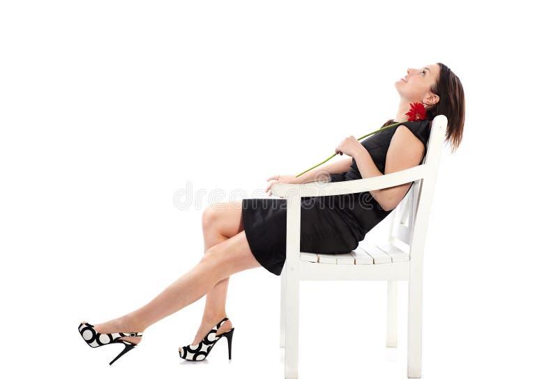 Szczęśliwy kobiety obsiadanie na drewnianym krześle z gerbera kwiatem i marzyć o weekendzie fotografia stock