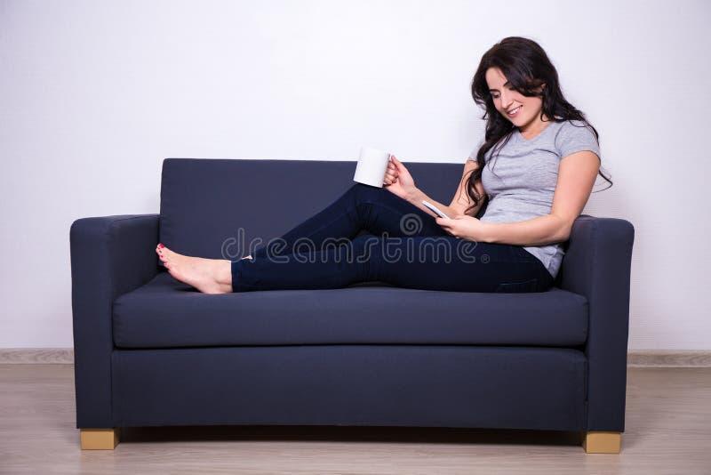 Szczęśliwy kobiety obsiadanie na kanapie z telefonem i kubkiem herbata zdjęcie royalty free
