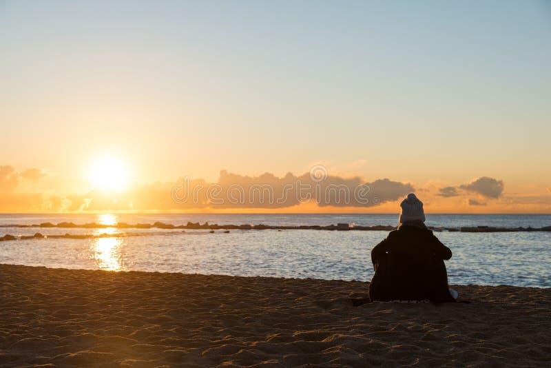 Szczęśliwy kobiety obsiadanie na zimno plaży z filiżanką herbata z światłami przy fotografia stock
