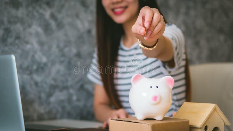 Szczęśliwy kobiety oszczędzania pieniądze w piggybank fotografia royalty free