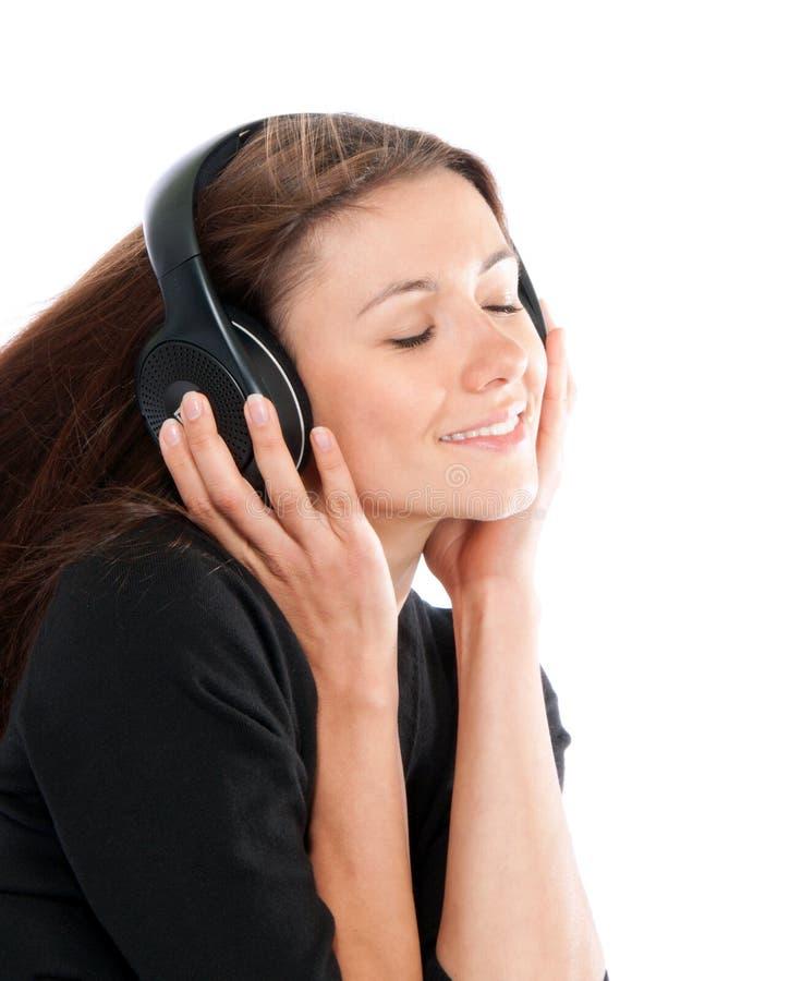 Szczęśliwy kobiety słuchanie i cieszy się muzykę w hełmofonach uśmiecha się oczy obraz royalty free