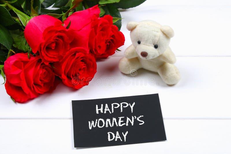 Szczęśliwy kobiety ` s dzień Marzec 8 Róże, miś i chalkboard na białym drewnianym stole, zdjęcie royalty free