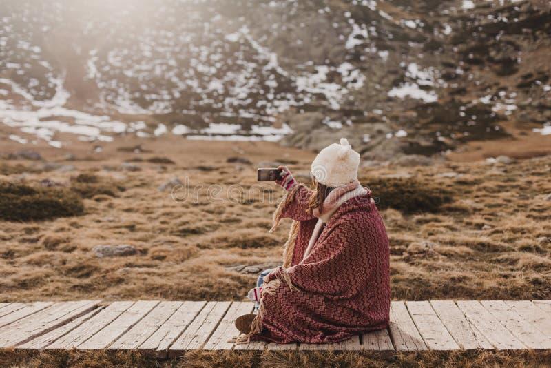 Szczęśliwy kobiety st zmierzch w naturze w jesieni używać telefon komórkowego zakrywającego z koc Zabawa outdoors fotografia stock