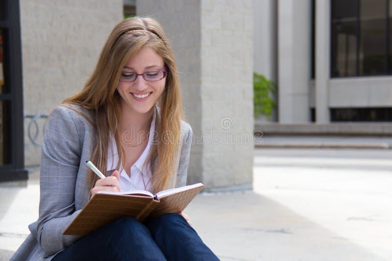 Szczęśliwy kobiety writing w jej czasopiśmie zdjęcia royalty free