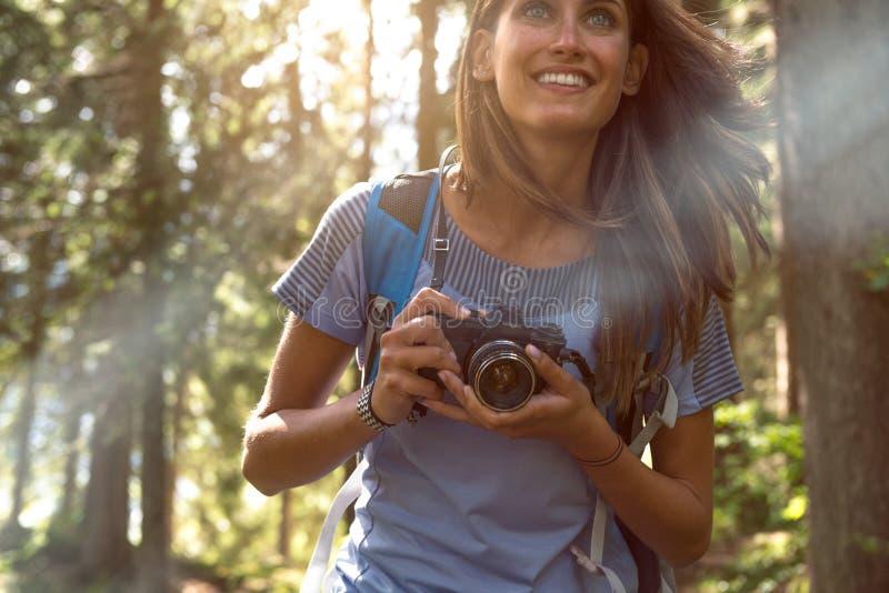 Szczęśliwy kobiety zbliżenie z rocznik kamery odprowadzeniem na wycieczkować ślad ścieżkę w lasowych drewnach podczas słonecznego obrazy stock