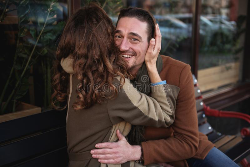 Szczęśliwy kochający pary obsiadanie na ławce i przytuleniu obraz stock