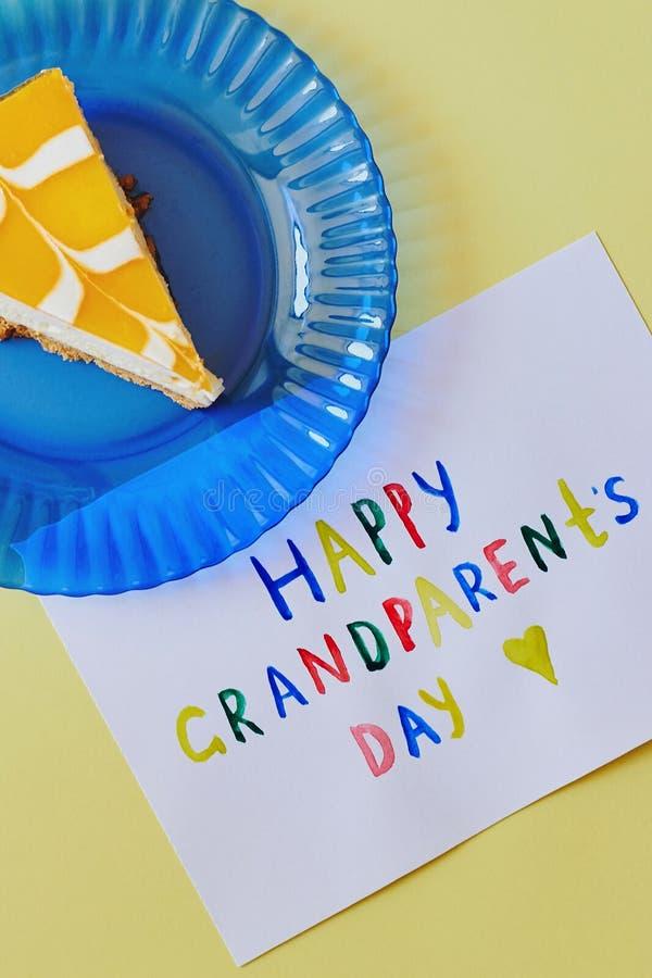 Szczęśliwy Krajowy dziadka dzień Barwiony kartka z pozdrowieniami robić dziećmi i kawałkiem tort na błękita talerzu jako prezent zdjęcia royalty free