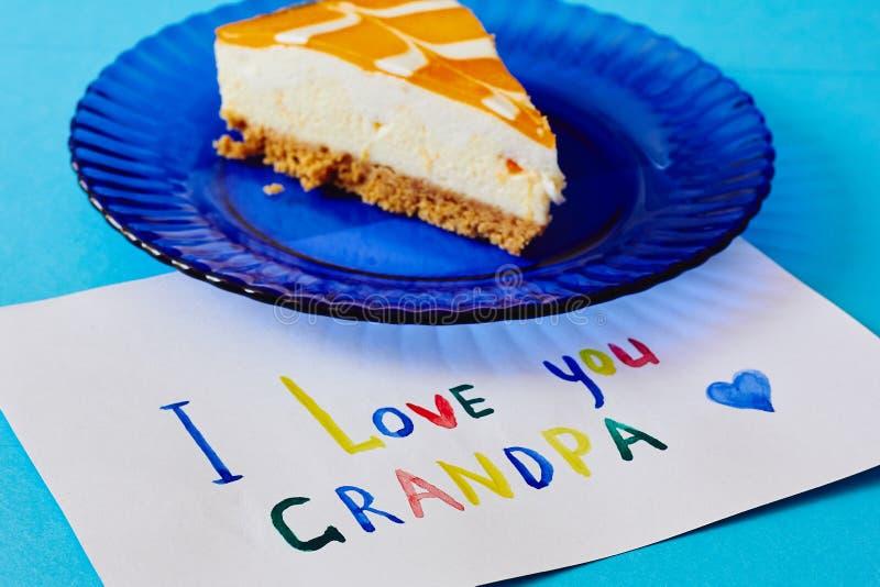 Szczęśliwy Krajowy dziadka dzień Barwiony kartka z pozdrowieniami robić dziećmi i kawałkiem tort na błękita talerzu jako prezent obraz royalty free