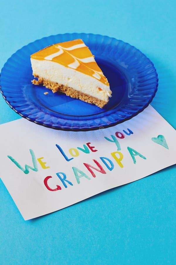 Szczęśliwy Krajowy dziadka dzień Barwiony kartka z pozdrowieniami robić dziećmi i kawałkiem tort na błękita talerzu jako prezent fotografia royalty free