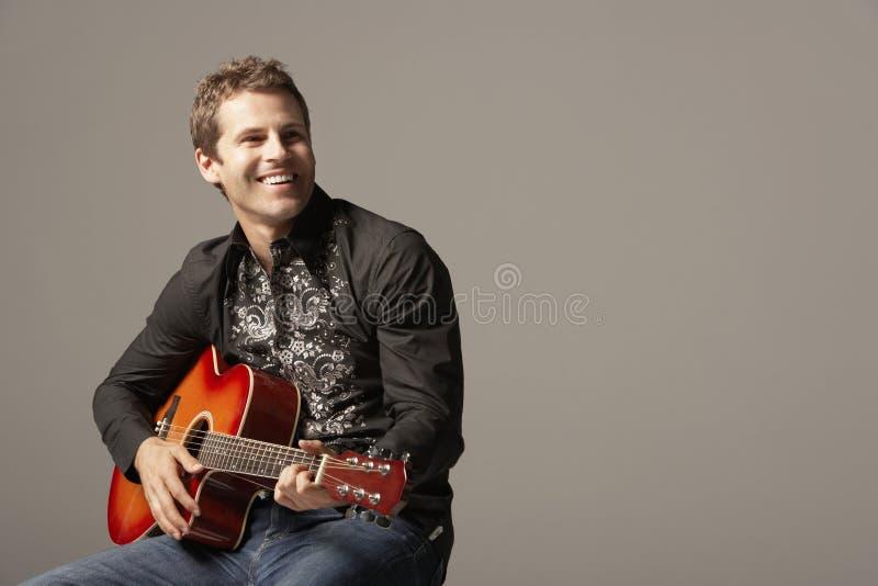 Szczęśliwy mężczyzna Bawić się gitarę obrazy stock