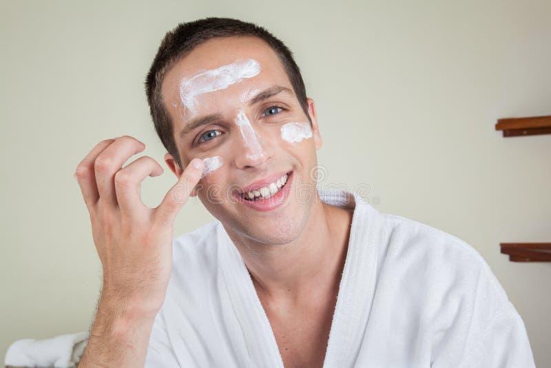 Szczęśliwy mężczyzna kładzenie na twarzy śmietance obraz royalty free