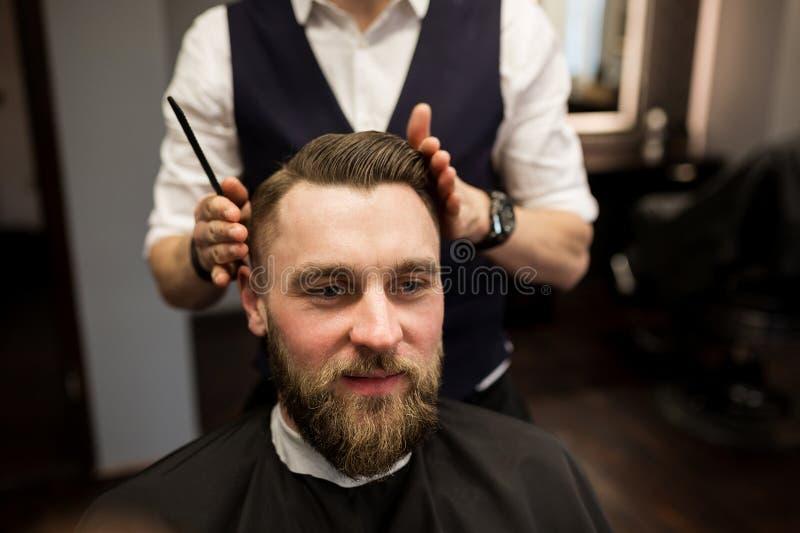 Szczęśliwy mężczyzna ma włosy ciącego przy fryzjera męskiego salonem fotografia stock