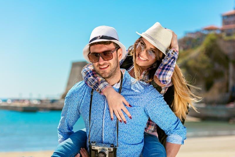 Szczęśliwy mężczyzna niesie jego dziewczyny na piggyback przejażdżce uśmiechniętej i patrzeje bardzo szczęśliwy cieszący się ich  obrazy royalty free