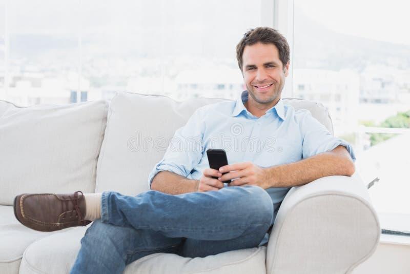 Szczęśliwy mężczyzna obsiadanie na leżance używać jego smartphone obrazy royalty free
