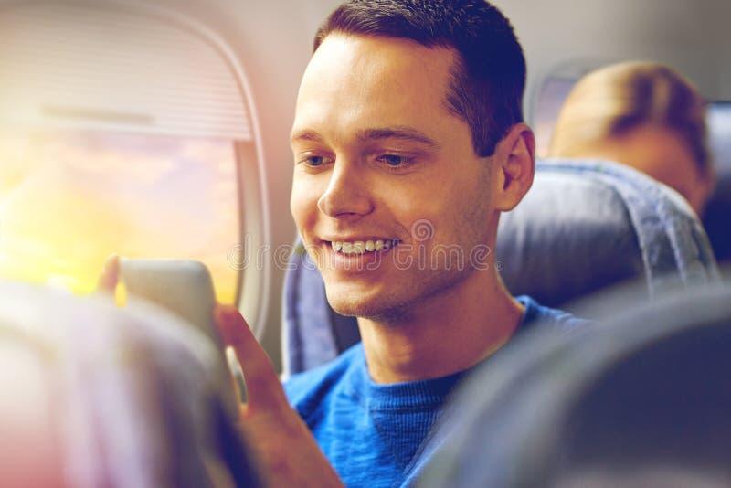 Szczęśliwy mężczyzna obsiadanie w samolocie z smartphone fotografia stock