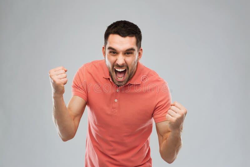 Szczęśliwy mężczyzna odświętności zwycięstwo nad szarym tłem obraz royalty free